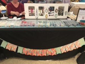 Custom banner and jewelry display at a local craft fair